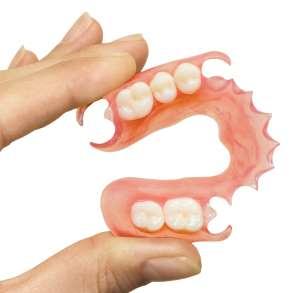 hand holding a flexible partial denture replacing front teett